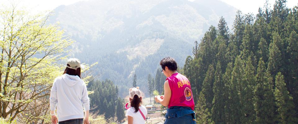 新緑の里山と子どもとお兄さんお姉さんと